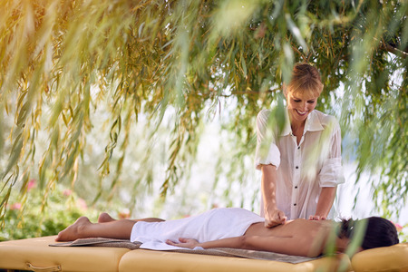Young smiling female receiving back massage from a massage professional at beauty salon in nature Stock Photo - 108581150
