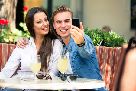 Smiling couple taking selfie in cafe, outdoor Foto de archivo - 108575343