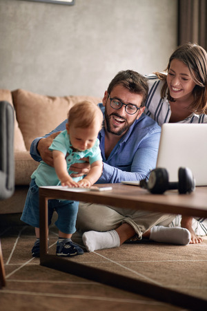Young parents with baby working from home using laptop