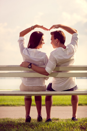 romantic couple makes heart symbol  with hands