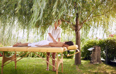 Beauty Spa Treatment in nature outdoor -Smiling masseur is massaging a female
