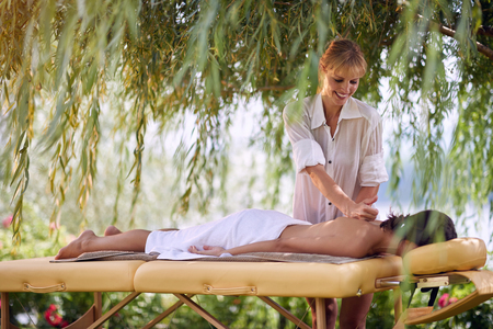 Massage therapy, healthcare concept, young woman lying on massage bed receiving a treatment from a professional masseur