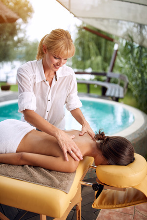 Massage - woman receiving back massage at home on outdoor Stock Photo