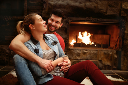 Happy hugging couple enjoying in mountain house near fire from fireplace 写真素材