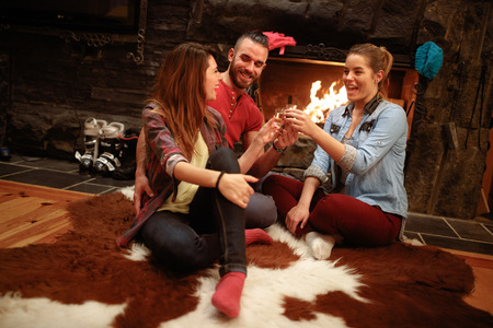 Cheerful young skiers toast by fireplace