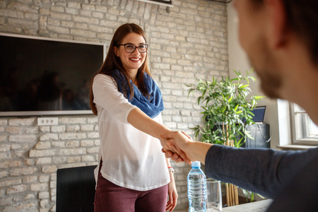Young woman shaking hands with male on job