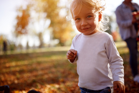 Sweet blond boy in park in autumn
