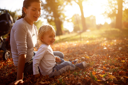 Male child with mother in park in fall
