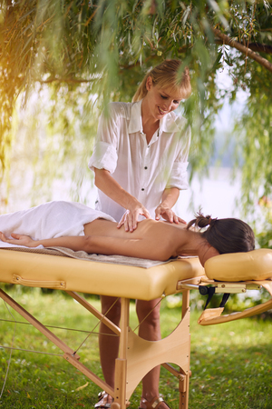 Young woman receiving relaxation massage in nature on outdoor
