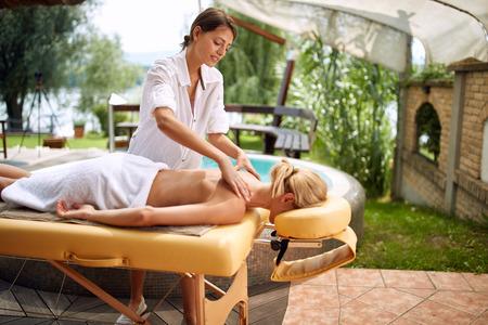 Massage - Beautiful woman in spa salon on outdoor getting massage