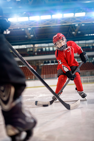 young boy play ice hockey in action kicking on goal