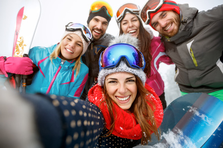 Happy group of skiers together taking selfie on mountain