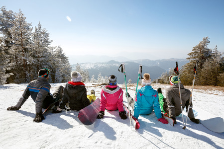 Skiers sitting on snow and resting from skiing, back view Stock Photo