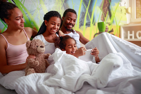 Happy African American family lying on bedroom in bed Stock Photo