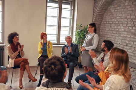 Coworkers applauding women in group meeting - support leadership