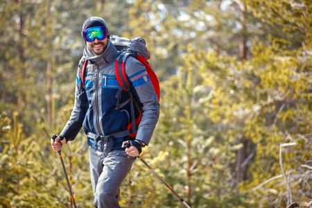 Smiling male hiking in snowy forest