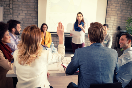 Female raises hand on business meeting for discussion