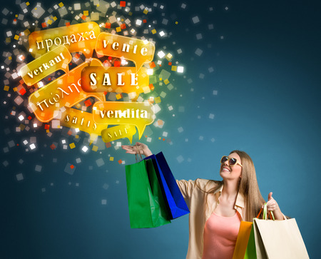 Smiling woman shopping with sale words international Stock Photo