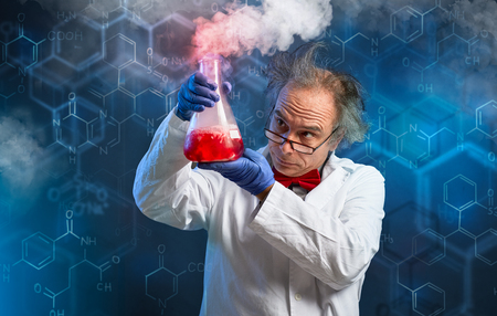Chemist carefully oversees his experiment over abstract Stock Photo