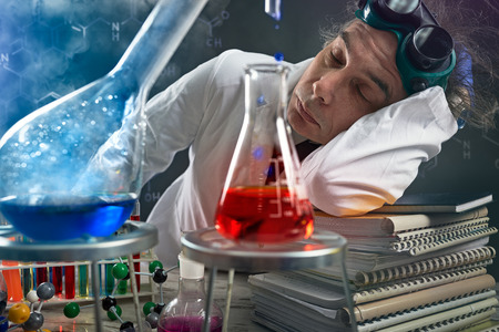 Very tired chemist sleeping at the time as it happens experimental Stock Photo