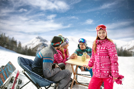 Smiling young girl with family in cafe on ski terrain enjoy 版權商用圖片