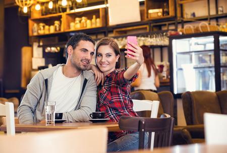 Couple taking self portrait in coffee shop Foto de archivo - 111267567