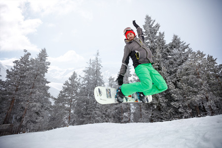 Fit snowboarder jumping with snowboard on ski terrain in mountain