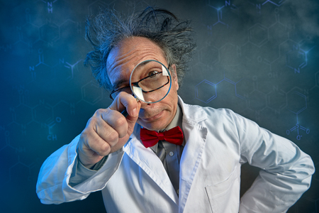 Funny scientist in white coat looking through a magnifying glass Banque d'images - 111267582