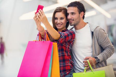 Pareja feliz tomando una foto en el centro comercial