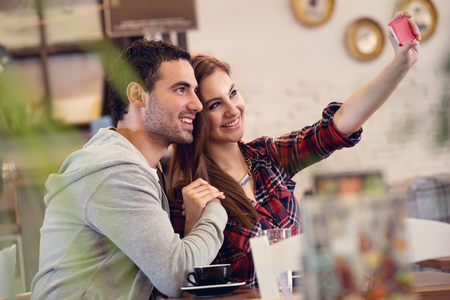 Beautiful loving couple taking selfie photo in cafe Foto de archivo - 111266828