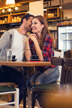 Cute young couple flirting  in cafe