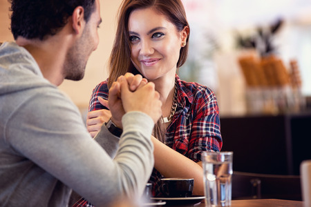 Amorous couple sitting on table and  looking each other in coffee shop