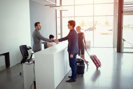 Młodzi biznesmeni przybywający do recepcji hotelu
