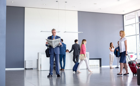 Male and female passengers wait for business class plain at airport Stock Photo