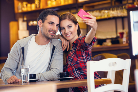 Young couple taking photo in cafe