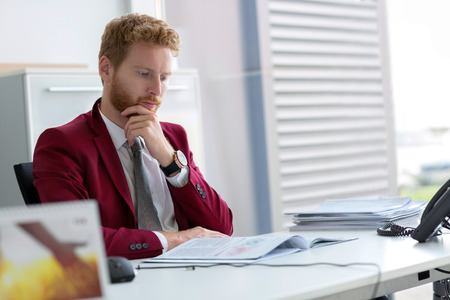 Young male employee at work in office Stock Photo