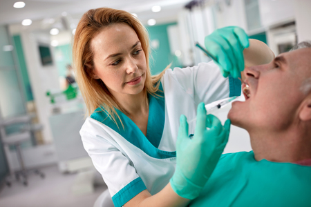 Female dentist in dental clinic giving anesthesia to senior male patient 스톡 콘텐츠