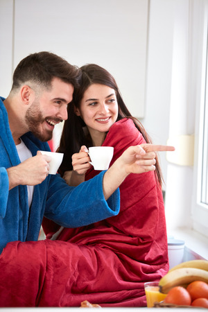 Couple looking through window in kitchen and drinks coffee