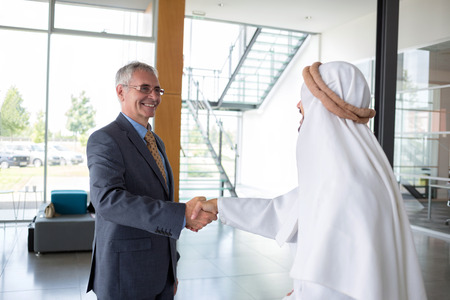 Mature businessman and Arabian partner handshake