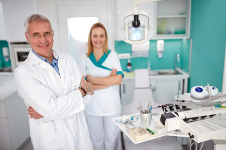 Portrait of senior dentist with nice female assistant in dental practice 스톡 콘텐츠