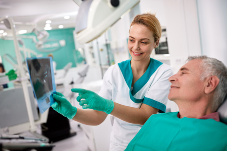 Male patient and female dentist looking at teeth X-ray in dental practice 스톡 콘텐츠 - 112072877