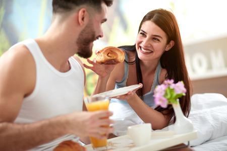 Couple enjoy in tasty croissant for breakfast in bed