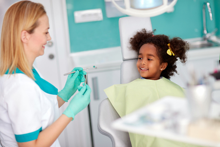 Female dental assistant show dental instruments to her young black female patient 스톡 콘텐츠 - 112072965