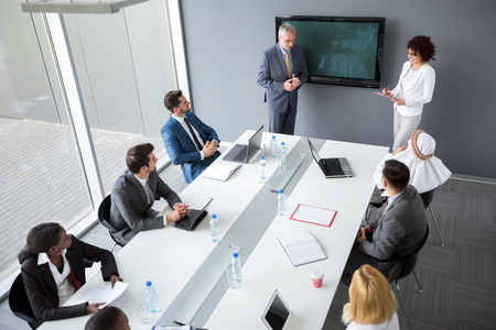 Male director and female assistant hold business meeting in  meeting room