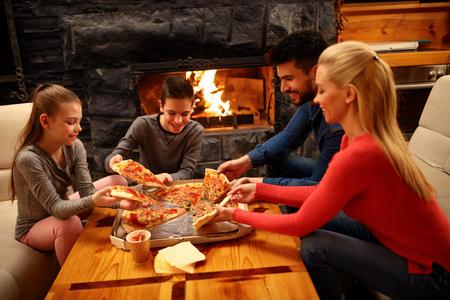 Famille heureuse mangeant de la pizza ensemble pour le dîner Banque d'images