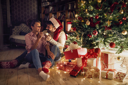 couple opening presents by shinny Christmas tree