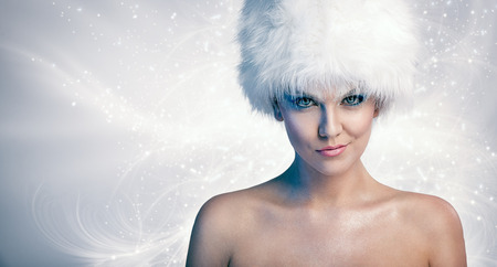 Cheerful naked woman with white winter hat