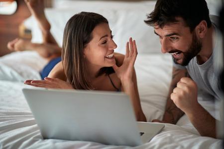 ベッドで面白い - ベッドでラップトップと幸せな若いカップル