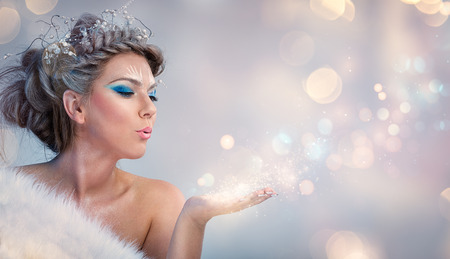 Beautiful winter woman blowing in the magic powder Stock fotó
