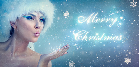 Beautiful snow queen blowing merry christmas